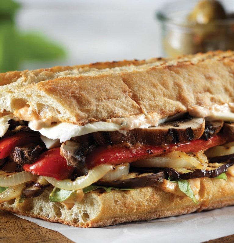 Sandwich sur baguette avec des étages de légumes grillés et de fromage