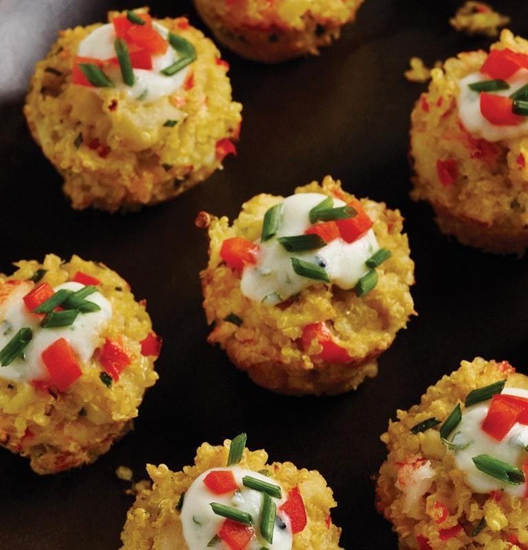 Plateau de beignets de crabe et de quinoa nappés de sauce et d'une garniture hachée
