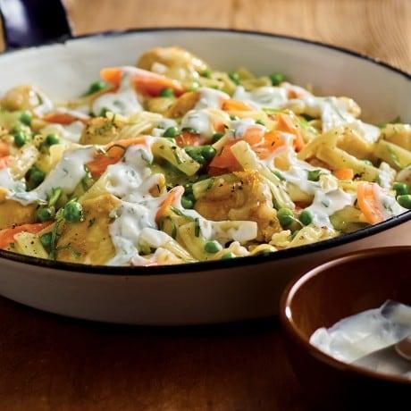 Des mains qui tiennent une poêle en fonte et servent un plat d'accompagnement de pâtes au beurre et aux fines herbes avec de la menthe hachée, des pois, des rondelles de carotte et du poulet