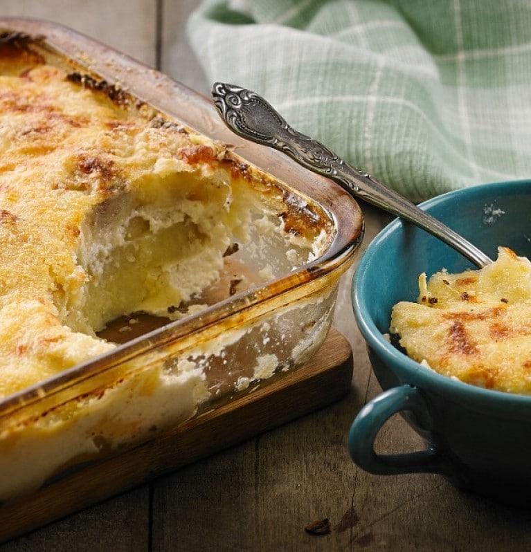 Travessa de batata temperada com alecrim, alho e Knorr sobre mesa de madeira