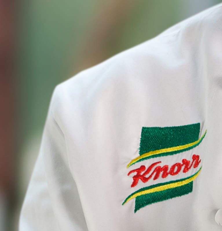 Close-up of an embroidered Knorr logo on a chef's jacket
