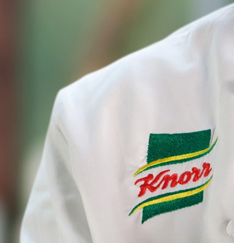 Gros plan sur le logo brodé de Knorr sur une blouse de chef