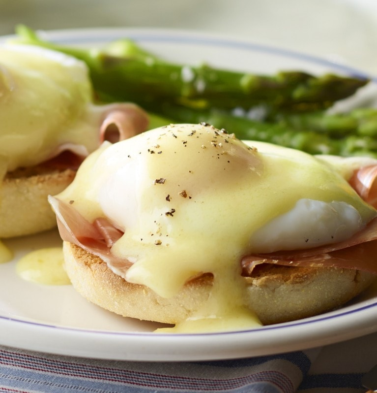 Eggs benedict with asparagus on the side and juice and fruit