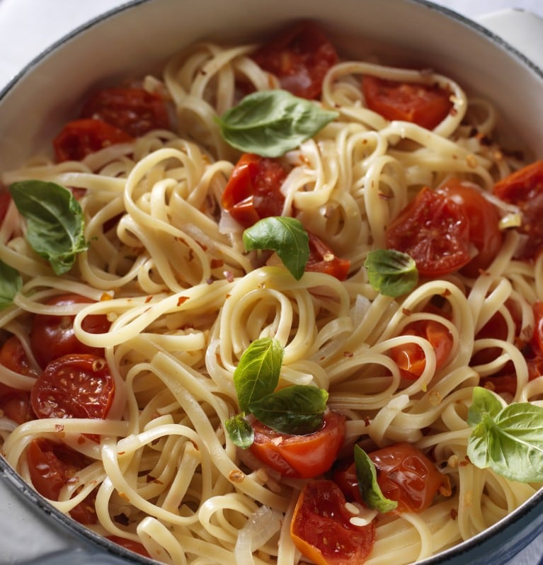 Spaghetti noodles in a bowl with tomatoes and green garnish